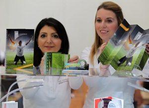 Zwei Damen stehen begeistert vor Notizbüchern mit Druck