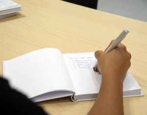 Eine Hand schreibt in ein Werbe-Notizbuch