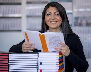 Viele Notizbücher als Werbemittel machen einer Frau sichtlich Freude